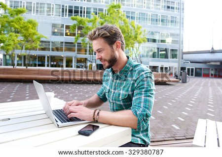 Portrait of an attractive man smiling with laptop outside - stock photo