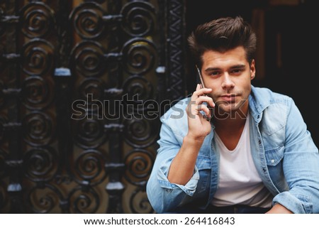 Portrait of an attractive man talking on his smart phone looking to the camera, handsome young man speaking on cellphone with copy space, fashionable man using his mobile phone in urban setting - stock photo