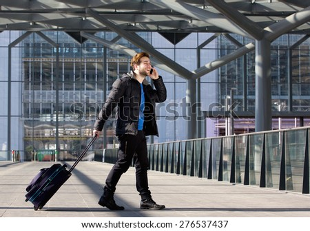 Portrait of an attractive man walking with suitcase and mobile phone at airport - stock photo