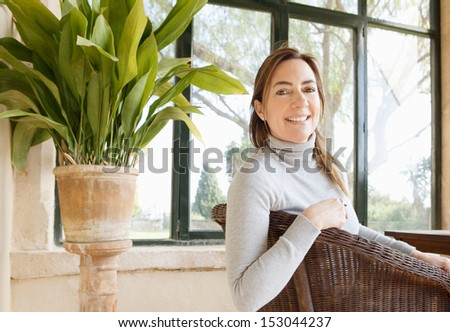 Portrait of an attractive mature woman sitting at a conservatory at home, turning to camera and smiling during a winter day, relaxing and lounging on a wicker chair, interior.  - stock photo