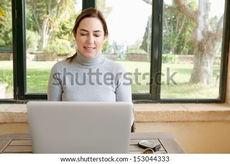 Portrait of an attractive mature woman sitting at a home conservatory garden glass windows relaxing and working on an open laptop computer during a sunny day, interior. - stock photo