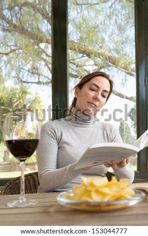 Portrait of an attractive mature woman sitting at a home conservatory garden glass windows relaxing and reading an open book while eating crisps and drinking red wine. - stock photo