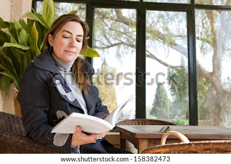 Portrait of an attractive mature woman sitting in a home conservatory with large glass windows and a green garden, holding and reading an open book and relaxing indoors. - stock photo
