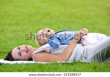 Portrait of an attractive mother lying down on grass with daughter - stock photo