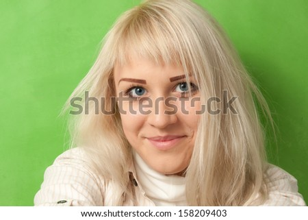 Portrait of an attractive smiling girl on a bright green background - stock photo