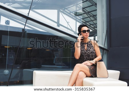 Portrait of an attractive successful woman entrepreneur speaking on her cell telephone while waiting for someone outdoors, female having mobile phone conversation while sitting near office building - stock photo
