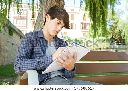 Portrait of an attractive teenager boy sitting on a wood park bench doing his college homework and studying writing notes during a sunny day. Outdoors student lifestyle. - stock photo