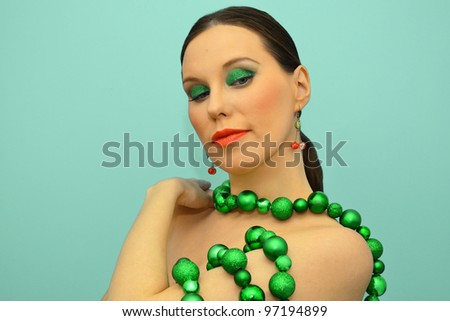 Portrait of an attractive woman in green decoration - stock photo