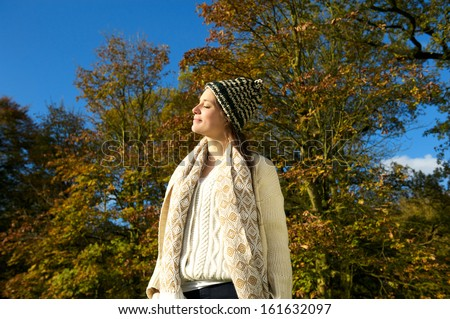 Portrait of an attractive woman in sweater and hat enjoying the sun on an autumn calm day - stock photo