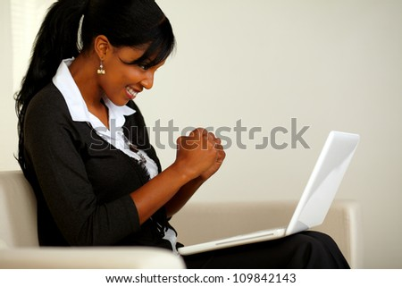 Portrait of an attractive woman on black suit celebrating a business victory while looking to her laptop and sitting on sofa at home - stock photo