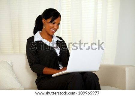 Portrait of an attractive woman on black suit working on laptop while sitting on couch at home indoor - stock photo