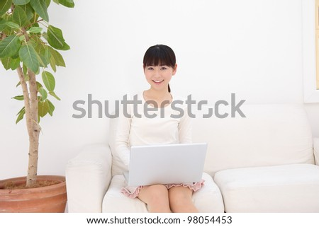 Portrait of an attractive young asian woman using laptop at home - stock photo