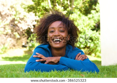 Portrait of an attractive young black woman lying on grass laughing - stock photo