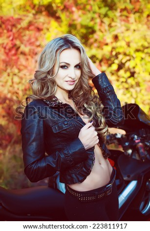 Portrait of an attractive young blond woman biker posing on her motorcycle. Healthy skin. Natural make-up.  - stock photo
