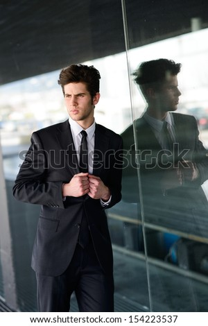 Portrait of an attractive young businessman in urban background - stock photo
