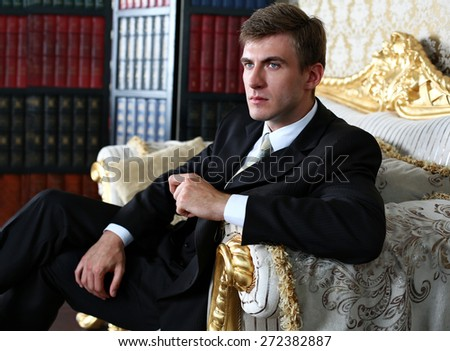 Portrait of an attractive young businessman in urban background wearinge suit a necktie. Blonde hair - stock photo