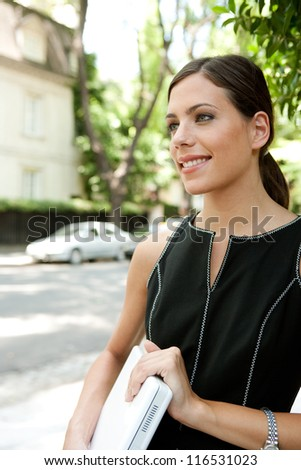 Portrait of an attractive young businesswoman holding a laptop computer under her arm while in a leafy street in the city with classic architecture. - stock photo
