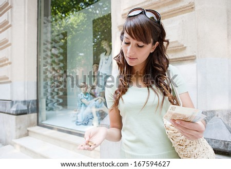 Portrait of an attractive young consumer woman holding notes and coins cash euros in her hands while standing by a store shop window display, counting her money for shopping. - stock photo