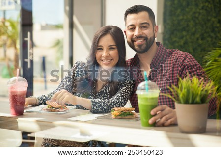 Portrait of an attractive young couple eating lunch together and smiling - stock photo
