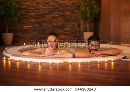 Portrait of an attractive young couple relaxing in a jakuzzi. - stock photo