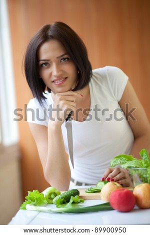 Portrait of an attractive young female cooking in the kitchen at home - stock photo