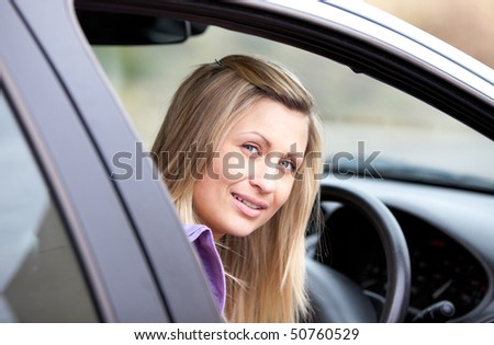 Portrait of an attractive young female driver sitting in her car - stock photo