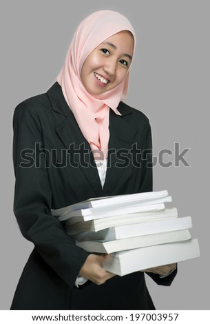 Portrait of an attractive young female office executive, carrying books with smile expression - stock photo