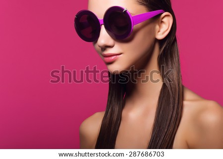 Portrait of an attractive young girl in round glasses on a pink background in studio - stock photo