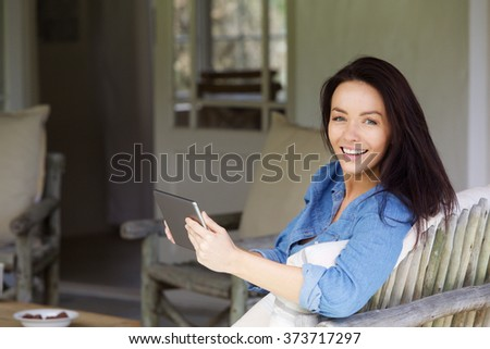 Portrait of an attractive young lady relaxing with touch screen tablet while sitting at home - stock photo