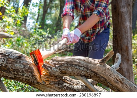Portrait of an attractive young lumberjack who chopping wood with an ax - stock photo