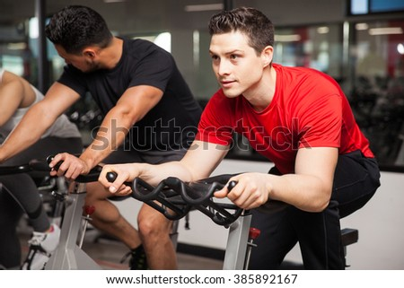 Portrait of an attractive young man doing some cardio on a bicycle and looking focused on his workout - stock photo