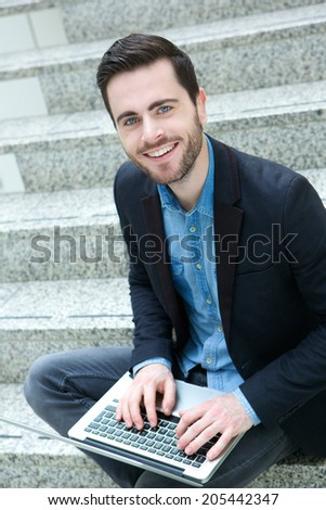 Portrait of an attractive young man sitting with laptop - stock photo