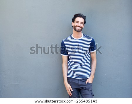 Portrait of an attractive young man smiling on gray background  - stock photo