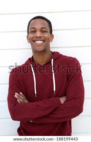 Portrait of an attractive young man smiling with arms crossed on white background - stock photo