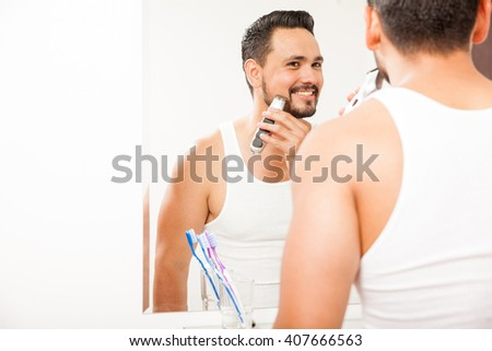 Portrait of an attractive young man using an electric razor to shave his beard in front of a bathroom mirror - stock photo