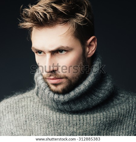 Portrait of an attractive young man with a beard in the studio in a warm sweater - stock photo