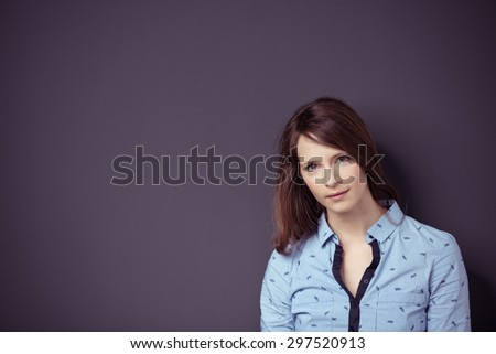 Portrait of an Attractive Young Woman Against Gray Wall with Copy Space, Looking at the Camera. - stock photo