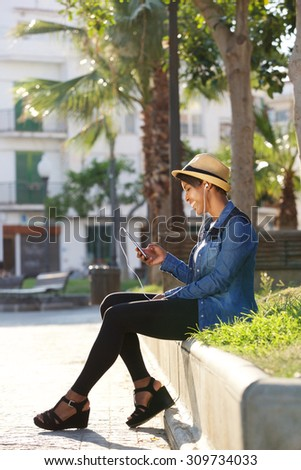 Portrait of an attractive young woman listening to music on mobile phone - stock photo