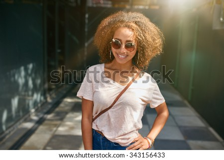Portrait of an attractive young woman posing with her hand on hip. Beautiful african woman in stylish casuals posing outdoors. - stock photo