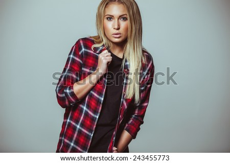 Portrait of an attractive young woman standing against white wall. Pretty young blond woman wearing shirt looking at camera. - stock photo