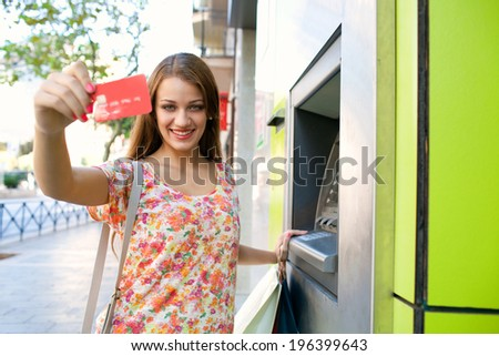 Portrait of an attractive young woman using a cash machine point to withdraw money, and showing off her credit card joyfully while carrying shopping bags during a sunny day in the city, lifestyle. - stock photo