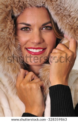 Portrait of an attractive young woman wearing a warm winter fur coat - stock photo