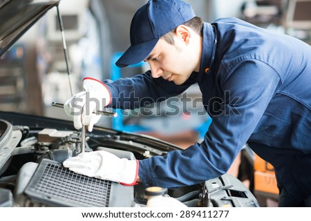 Portrait of an auto mechanic at work on a car in his garage - stock photo