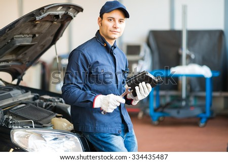 Portrait of an auto mechanic holding a jug of motor oil and a wrench - stock photo