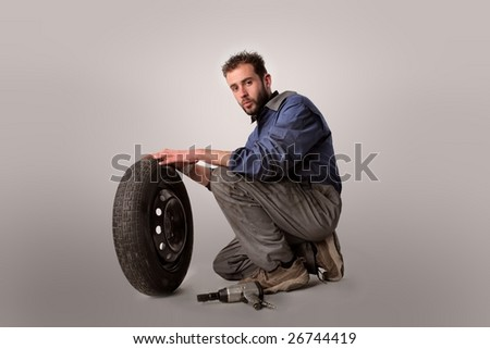 Portrait of an  auto mechanic with wheel and gun isolated on a white background - stock photo