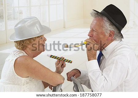 Portrait of an elderly couple in festivity blowing and making noise - stock photo