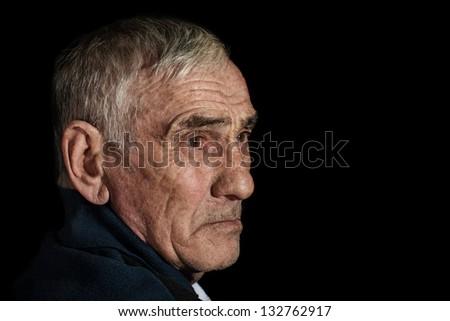 portrait of an elderly man on black background - stock photo