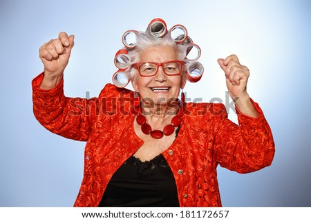 Portrait of an elderly woman in curlers looking at camera. - stock photo