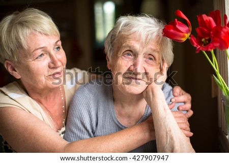 Portrait of an elderly woman of eighty years with her daughter. - stock photo