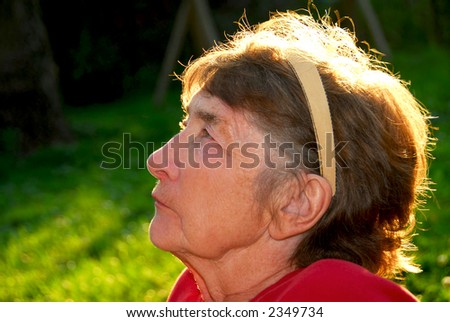 Portrait of an elderly woman outside with backlit hair - stock photo